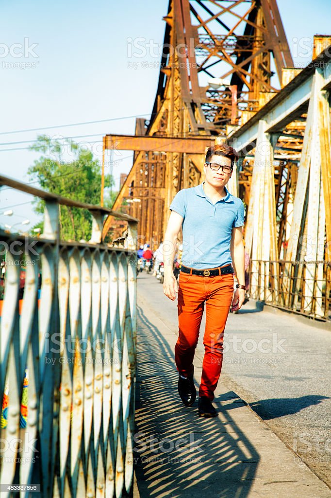 Confident young Vietnamese man crossing Long Bien bridge Full Length stock photo