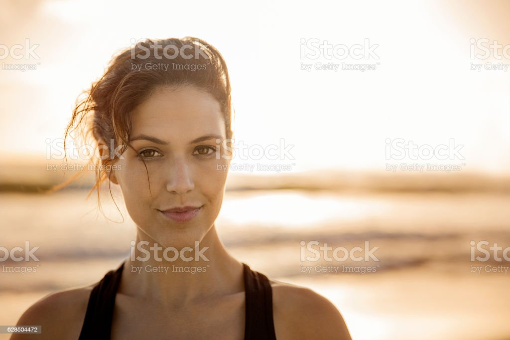 Confident young woman at beach during sunset – Foto