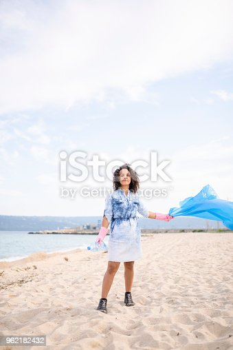 962184460 istock photo Confident young woman during local clean up at the beach 962182432
