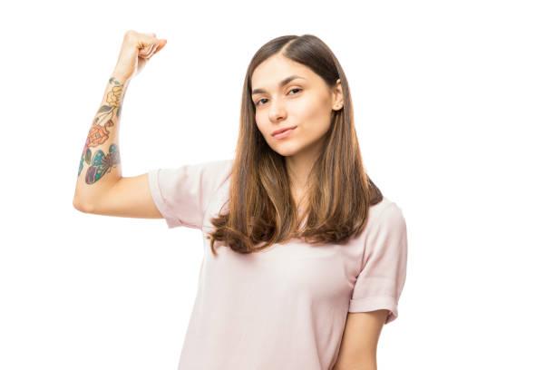 selbstbewusste junge frau biegen ihren bizeps - tattoos frauen arm stock-fotos und bilder