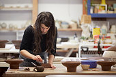 Young woman making pottery at workshop. Concentrated female owner is working in pottery studio. She is wearing casuals.