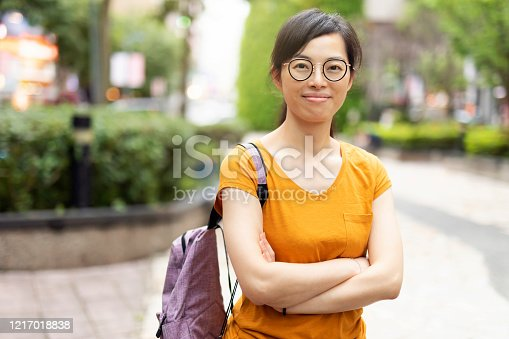 Portrait of a young and naturally beautiful Taiwanese ethnicity woman with eye glasses and a ponytail.