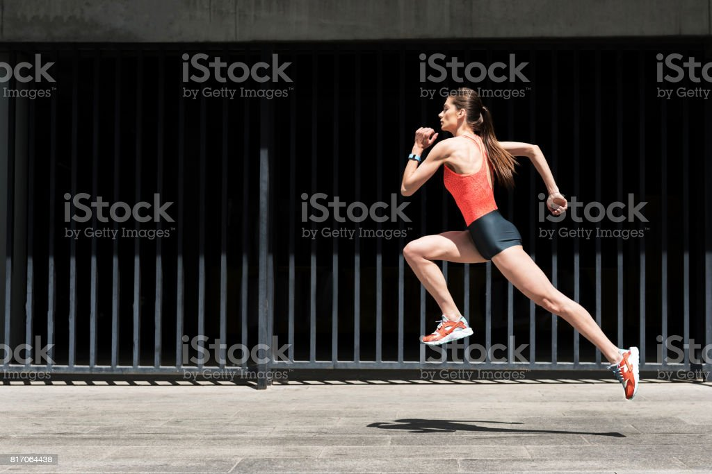 Confident young woman running outdoors stock photo