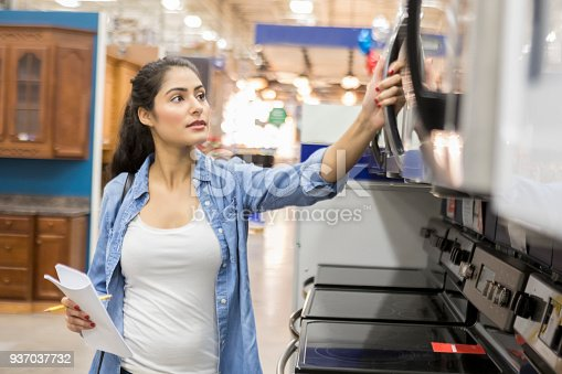 istock Confident young woman shopping for microwave oven 937037732