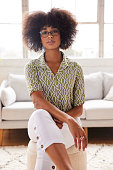 istock Confident young woman sitting on stool in her sunny living room 1289313309