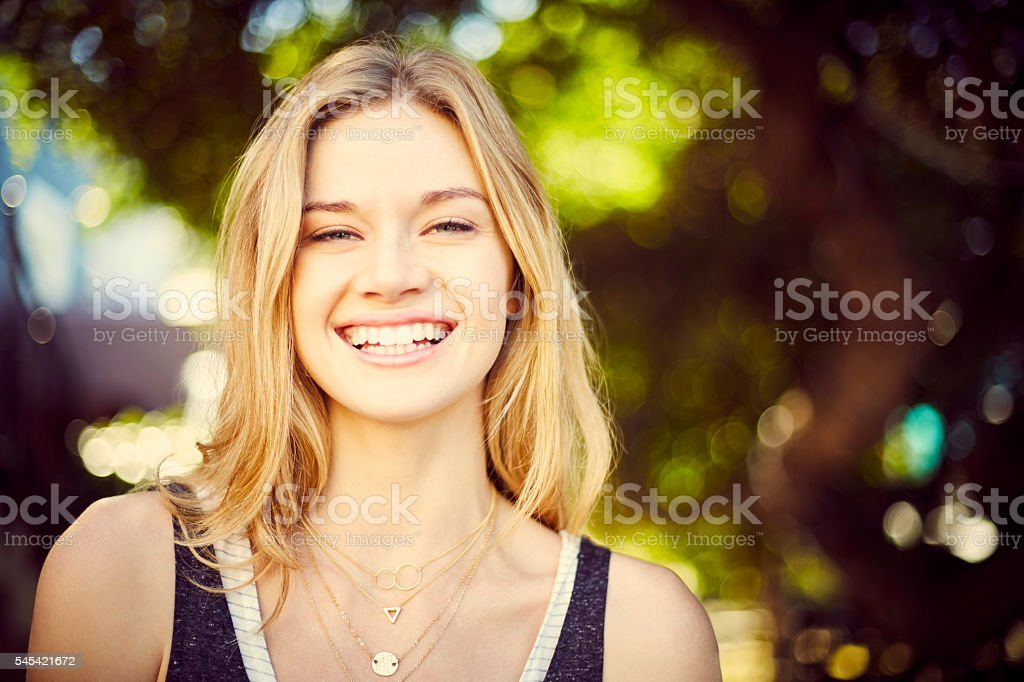 Confident young woman smiling on city street stock photo