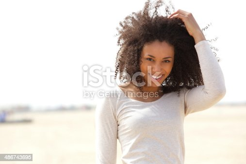 istock Confident young woman smiling outdoors 486743695