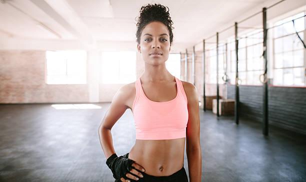confident young woman standing in gym - brassière de sport photos et images de collection