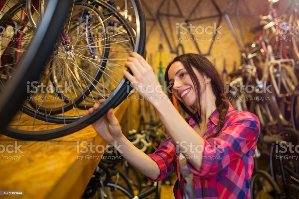 Confident Young Woman Working In A Bicycle Repair Shop Stock Photo -  Download Image Now