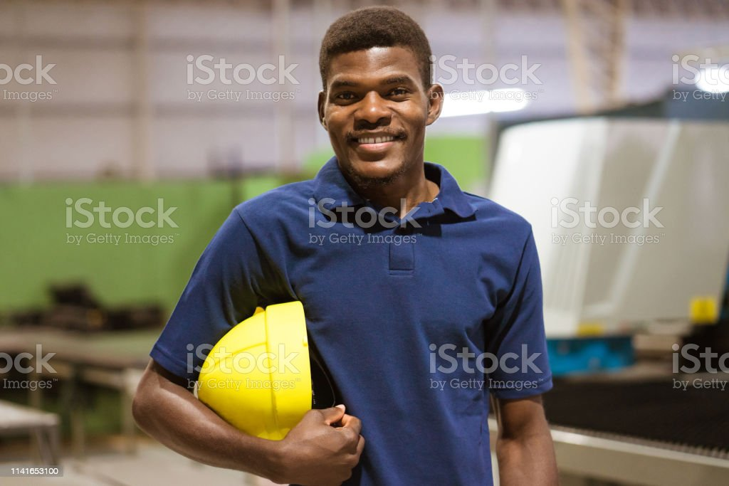 Confident young worker in industry Portrait of confident worker holding hardhat. Young male is standing in factory. He is wearing blue uniform. 25-29 Years Stock Photo