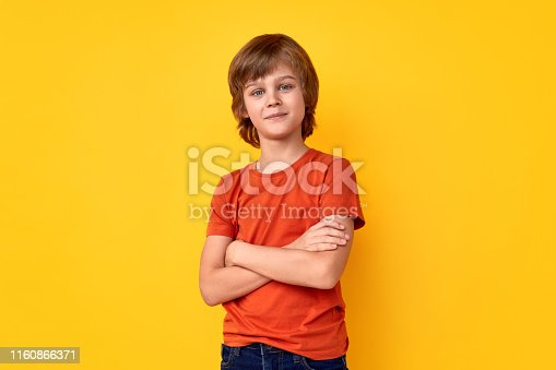 Positive preteen boy in casual outfit keeping arms crossed and looking at camera against vivid yellow background