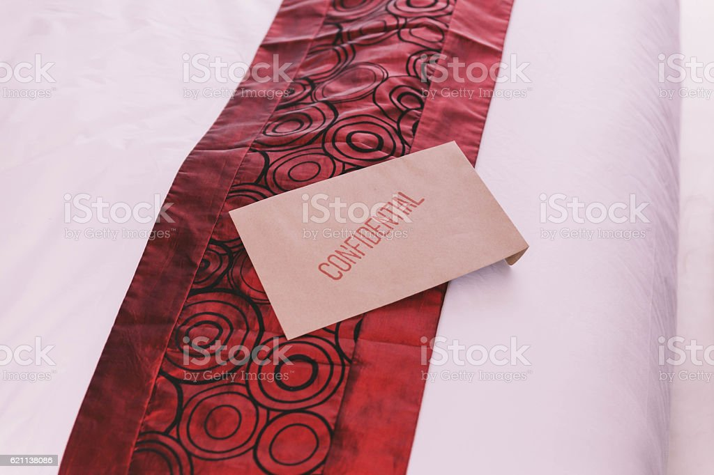 Confidential Brown Envelop on The Bed. stock photo