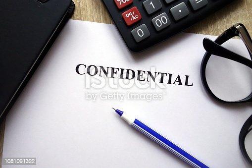 Confidential document, calculator, pen and glasses on desk