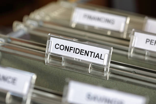 Confidential file Inside of a filing cabinet with green folders and focus on confidential label privacy stock pictures, royalty-free photos & images