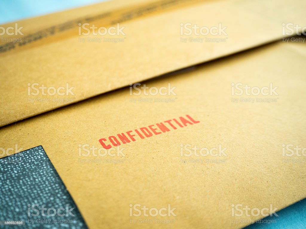 'Confidential' printed on brown vintage envelope, in macro stock photo