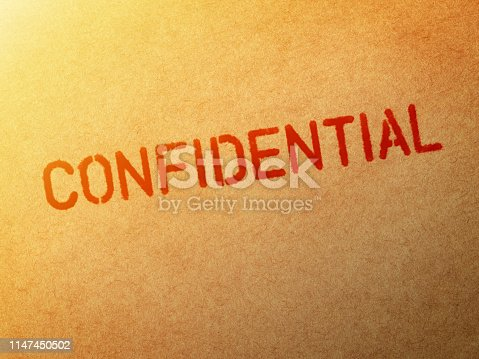 Close-up of word Confidential stamped on brown paper.