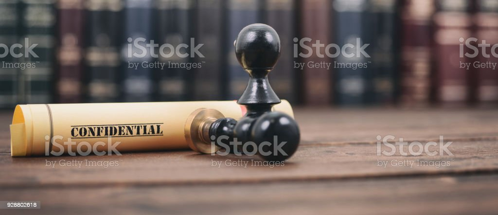 Confidential type of document and notary seals on the wooden background. stock photo