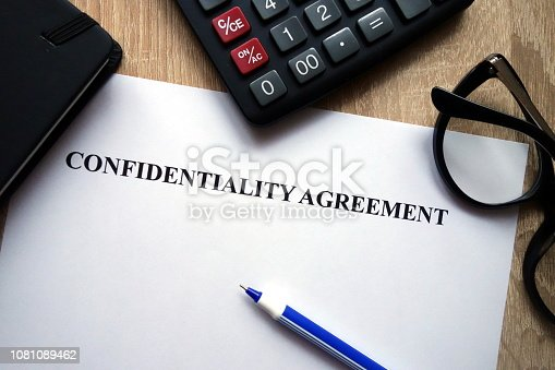 Confidentiality agreement, calculator, pen and glasses on desk
