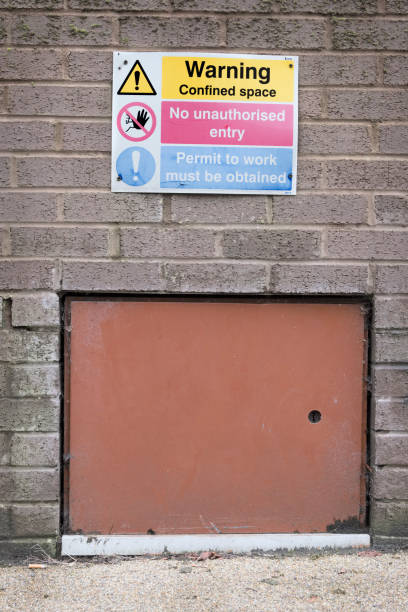 Confined space no unauthorised access building site health safety sign Confined space no unauthorised access building site health safety sign at workplace for workers in construction confined space stock pictures, royalty-free photos & images
