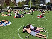 Brooklyn, NY, USA May 24, 2020 Friends, family and couples are confined to circles on the lawn of Domino Park in Williamsburg, Brooklyn, New York
