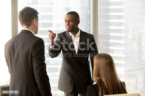 istock Conflict between male black and white office workers at workplace 695760162