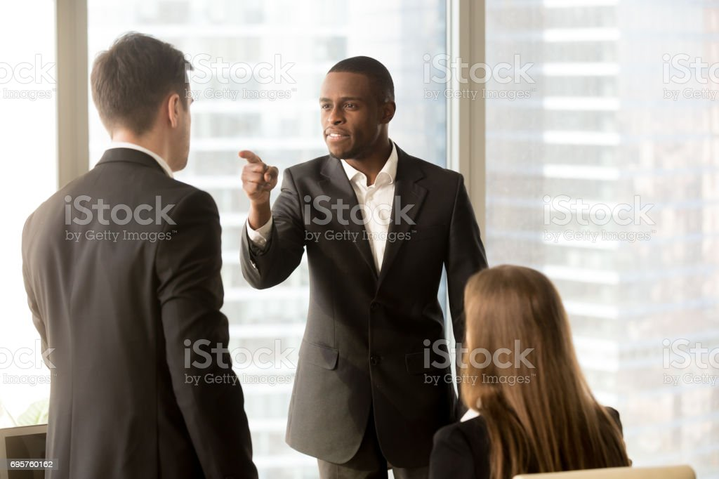 Conflict between male black and white office workers at workplace stock photo