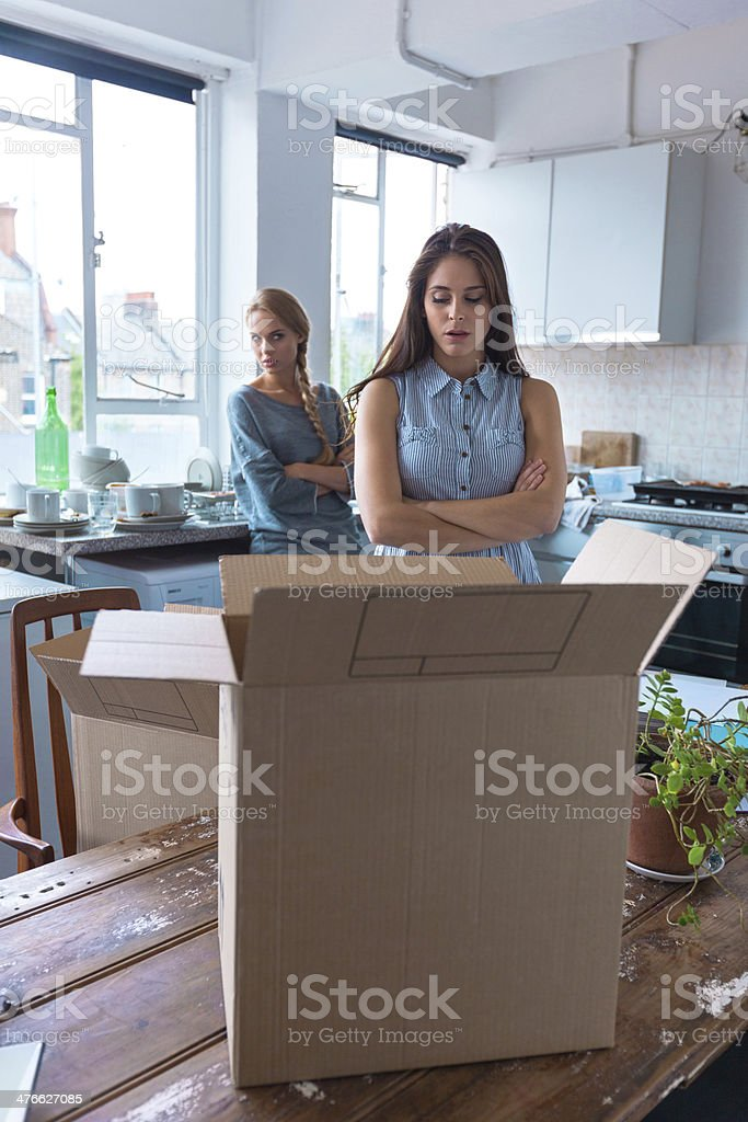 Conflict between roommates Two girls having quarrel at home. Cardboard box in the foreground. 20-24 Years Stock Photo