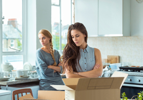 Two girls having quarrel at home, giving up the cohabitation. Cardboard boxes on the table.