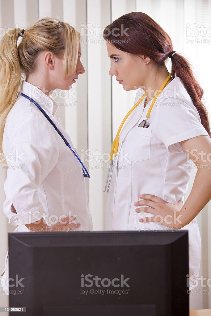 conflict between two women doctors stock photo