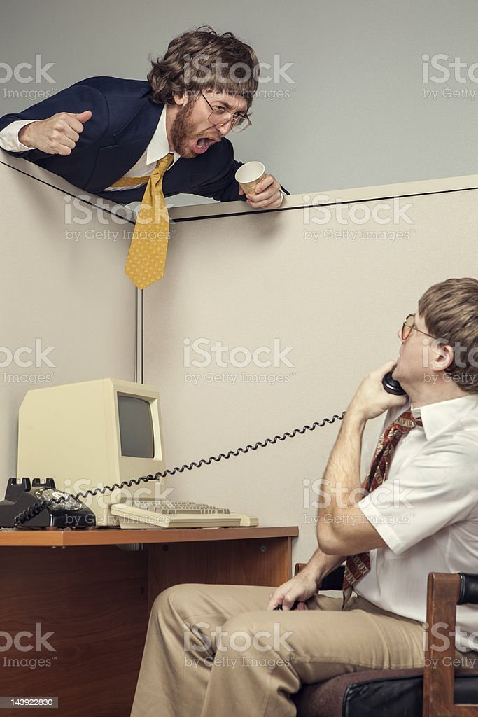 A manager in full suit leans over an office cubicle and yells at his...