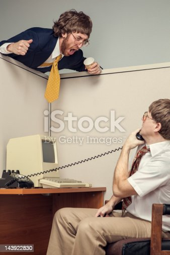 A manager in full suit leans over an office cubicle and yells at his co-worker, looking very angry.  The other business man is on a phone call and stares at the yelling man.  1980's styling, complete with vintage computer.  Vertical.