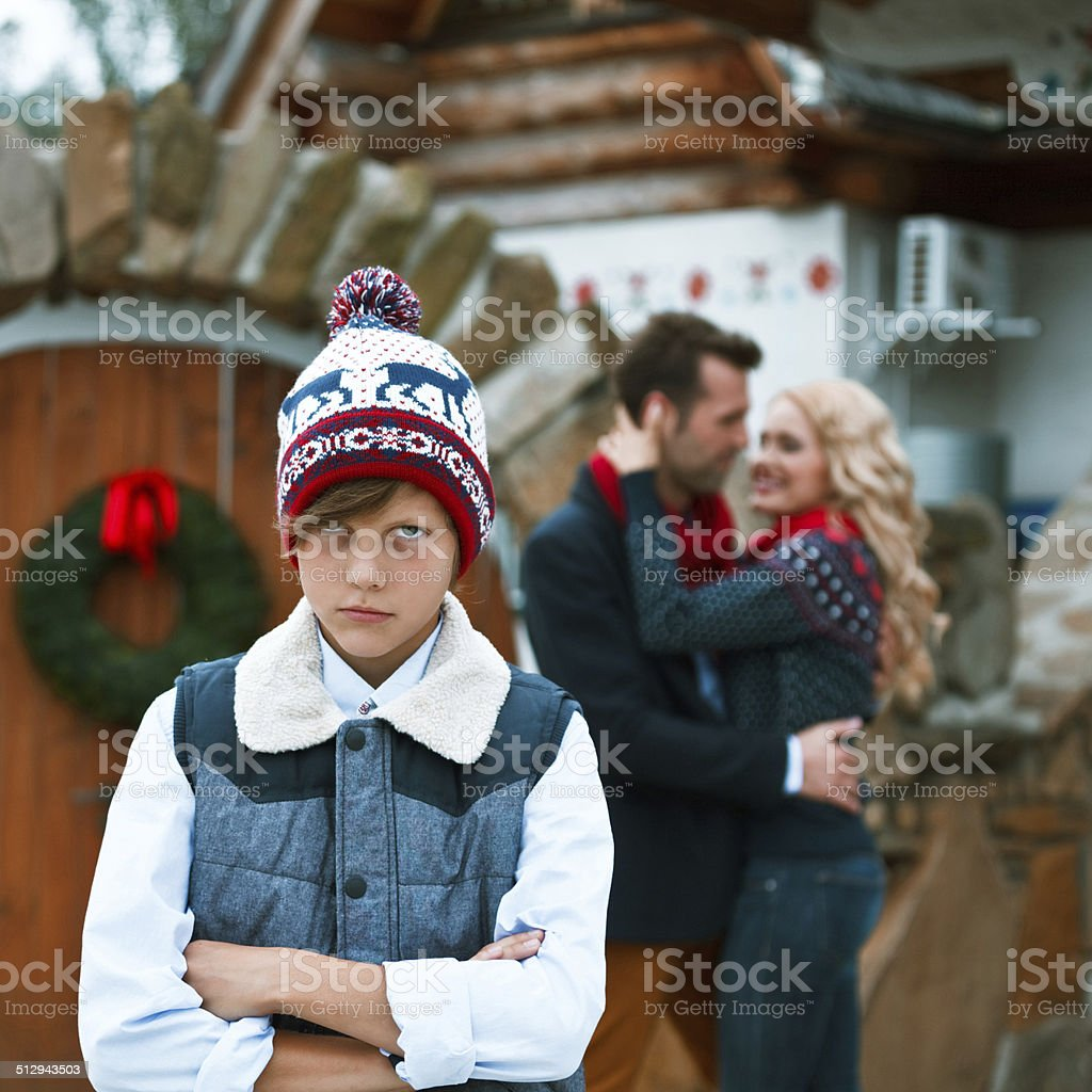 Conflict in family An angry boy standing with arms crossed with his parents embracing in the background.  10-11 Years Stock Photo