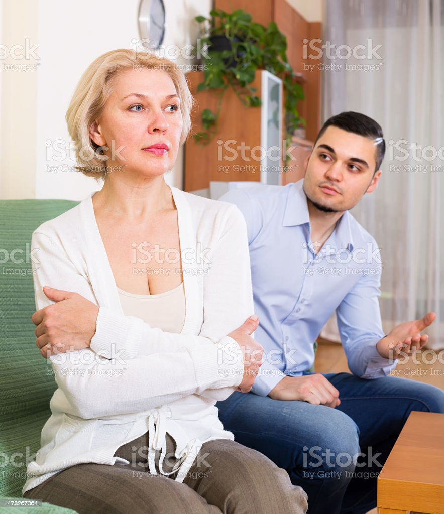 Conflict of aged woman and young guy stock photo