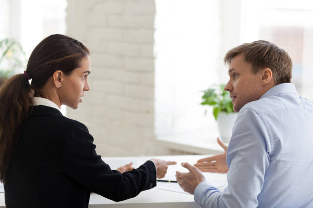 Conflict of female boss and male office worker stock photo