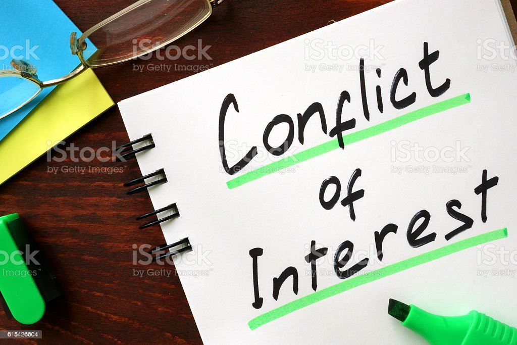 Conflict of interest sign written in a notepad. stock photo
