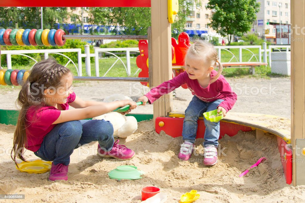 Conflict on the playground. Two kids fighting over a toy in the sandbox stock photo