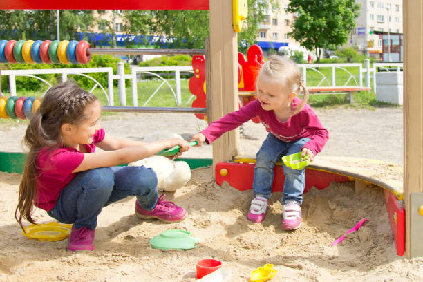 conflict on the playground. two kids fighting over a toy in the sandbox - fighting stock photos and pictures