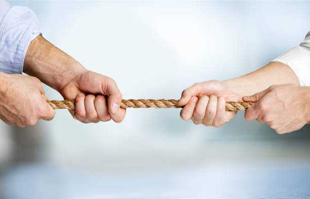 Conflict. Business people pulling rope in opposite directions at office pulling stock pictures, royalty-free photos & images