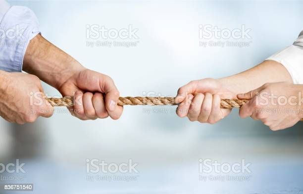 Business people pulling rope in opposite directions at office