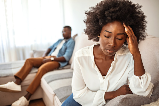 Unhappy Couple After an Argument in the Living Room at Home. Sad Pensive Young Girl Thinking of Relationships Problems Sitting on Sofa With Offended Boyfriend, Conflicts in Marriage,