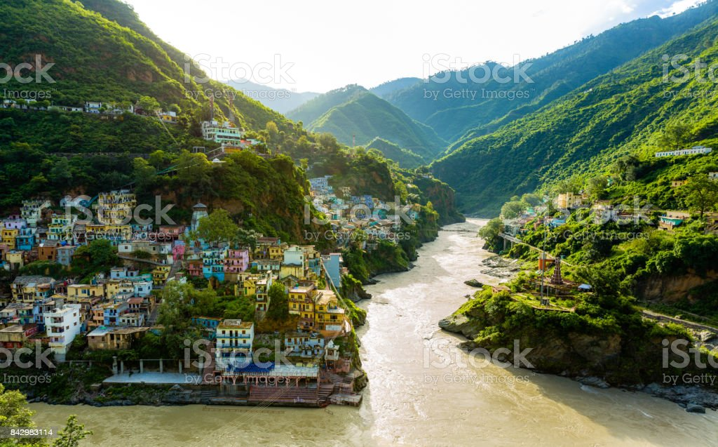 Confluence of two rivers Alaknanda and Bhagirathi give rise to the holy river of Ganga / Ganges at one of the five Prayags called Dev Prayag. Lush greenery in monsoons on the mountains. sunrise. India stock photo