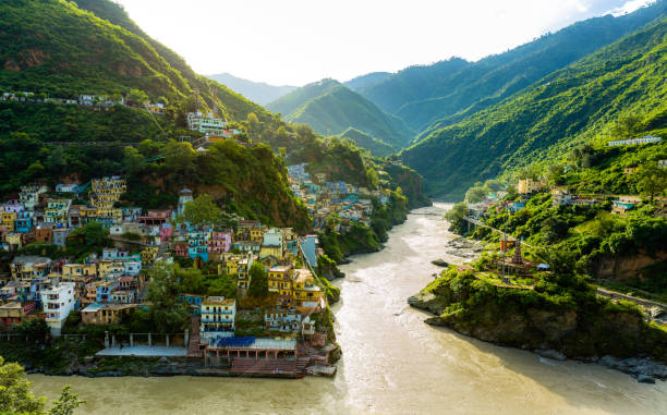 confluence of two rivers alaknanda and bhagirathi give rise to the holy river of ganga / ganges at one of the five prayags called dev prayag. lush greenery in monsoons on the mountains. sunrise. india - india foto e immagini stock