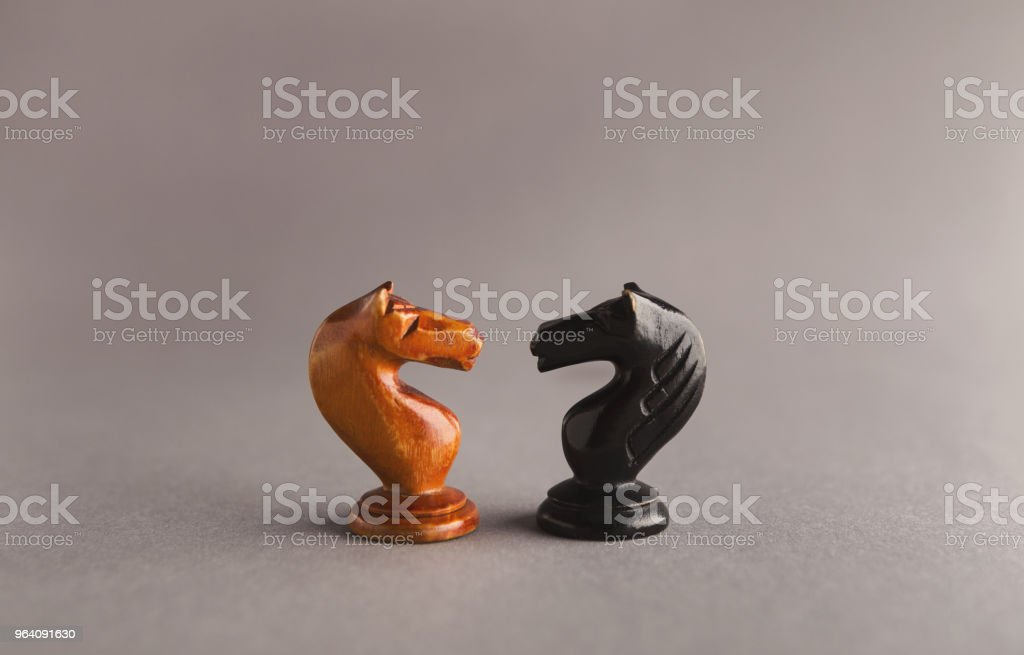 Confrontation of chess pieces on gray background - Royalty-free Anthropomorphic Face Stock Photo