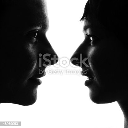 Black and white profiles of young man and woman standing face to face close to each other and looking into eyes. Isolated on white background.