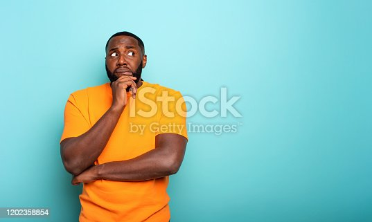 Confuse and pensive expression of a black boy. cyan colored background