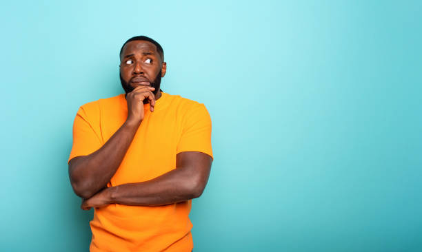Confuse and pensive expression of a boy . cyan colored background stock photo