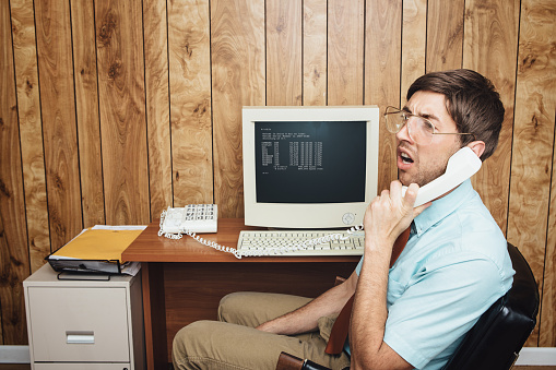 A man and office in 1980's - 1990's style, complete with vintage computer and technology of the time, listens with a look of confusion or boredom to someone on the phone.  Wood paneling on the wall in the background.  Horizontal with copy space.