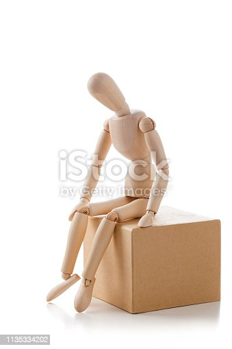 Wooden mannequin sitting on cardboard box looking down with one hand on head like worried or thinking. The composition is isolated on white background. Predominant colors are brown and white. High key DSRL studio photo taken with Canon EOS 5D Mk II and Canon EF 100mm f/2.8L Macro IS USM.