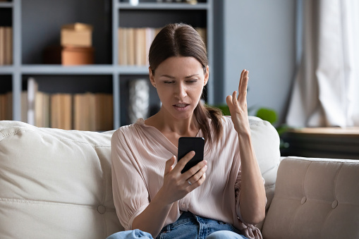 Confused angry woman having problem with phone, sitting on couch at home, unhappy young female looking at screen, dissatisfied by discharged or broken smartphone, reading bad news in message