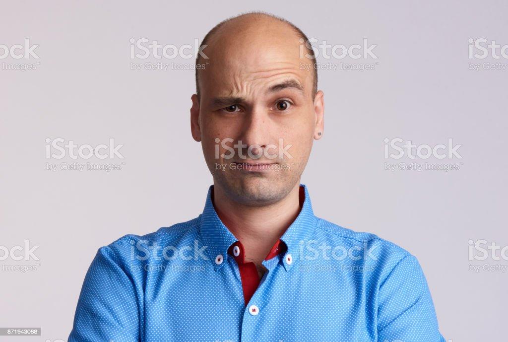confused bald man raised eyebrow. stock photo